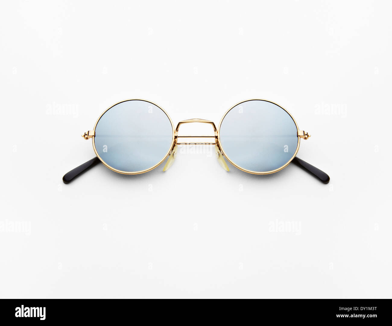 2f3d84188cdfe Round mirrored sunglasses with gold rims still life photograph against a  white background - Stock Image