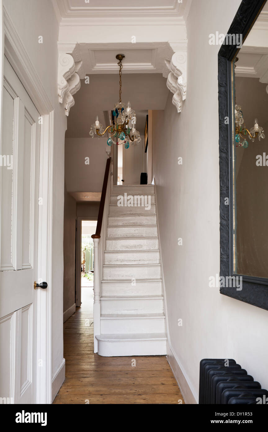 White wooden staircase in hallway with corbels and blue drop chandelier. - Stock Image