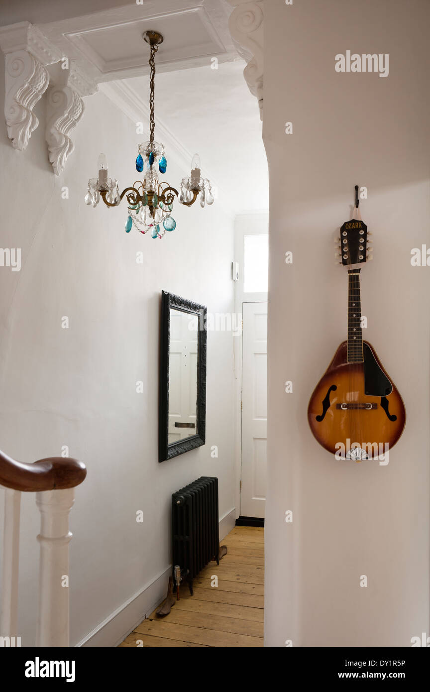 A mandolin hangs on the wall of an entrance hall with corbels and blue drop chandelier - Stock Image
