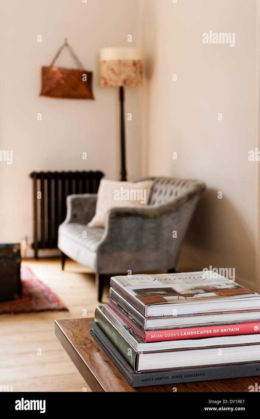 Pile of books on wooden coffee table with buttoned sofa and old radiator in background - Stock Image