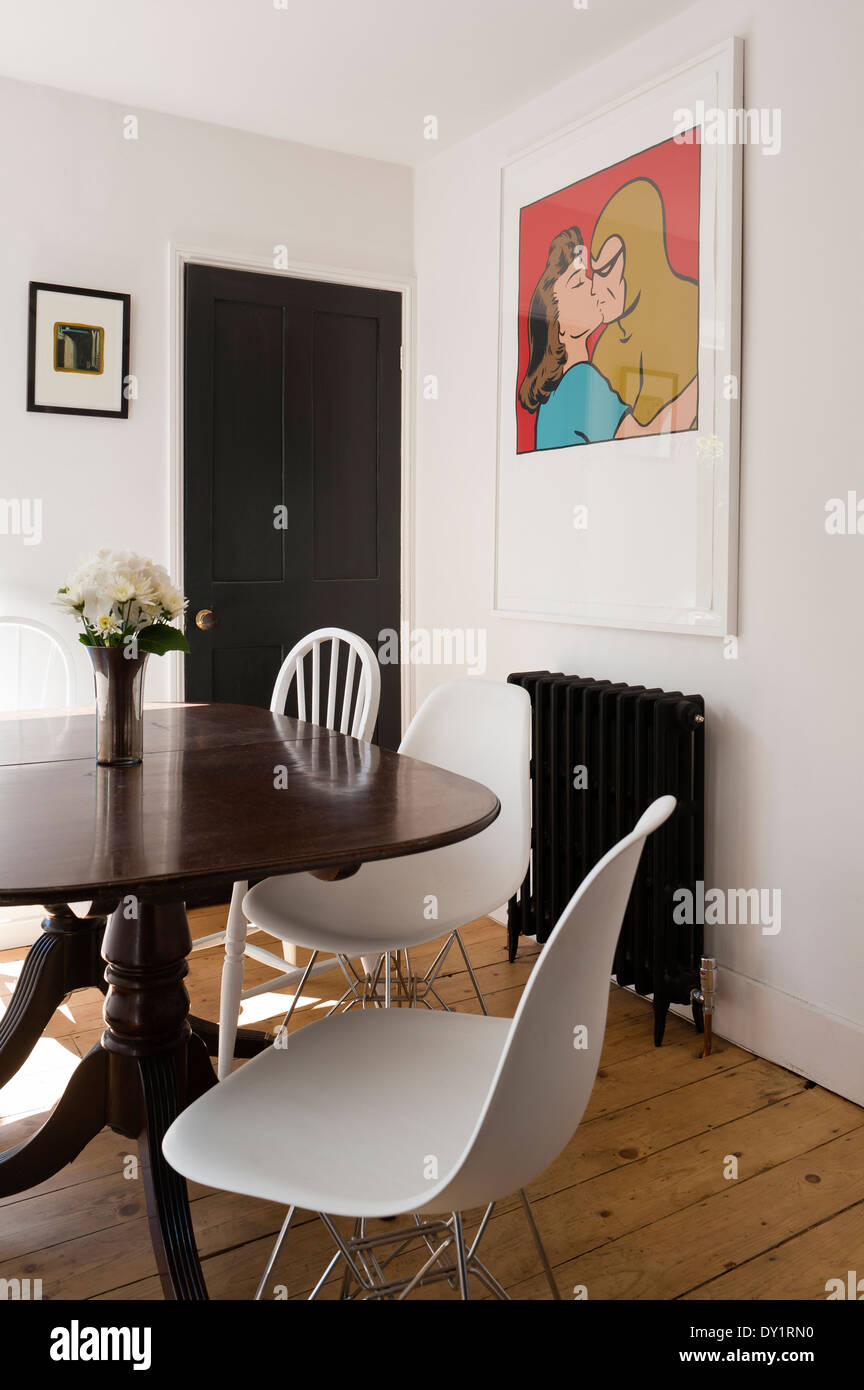 Antique mahogany tilt-top table in dining room with white Eames DSR chrome  base chairs - Old Pine Table Chairs In Stock Photos & Old Pine Table Chairs In