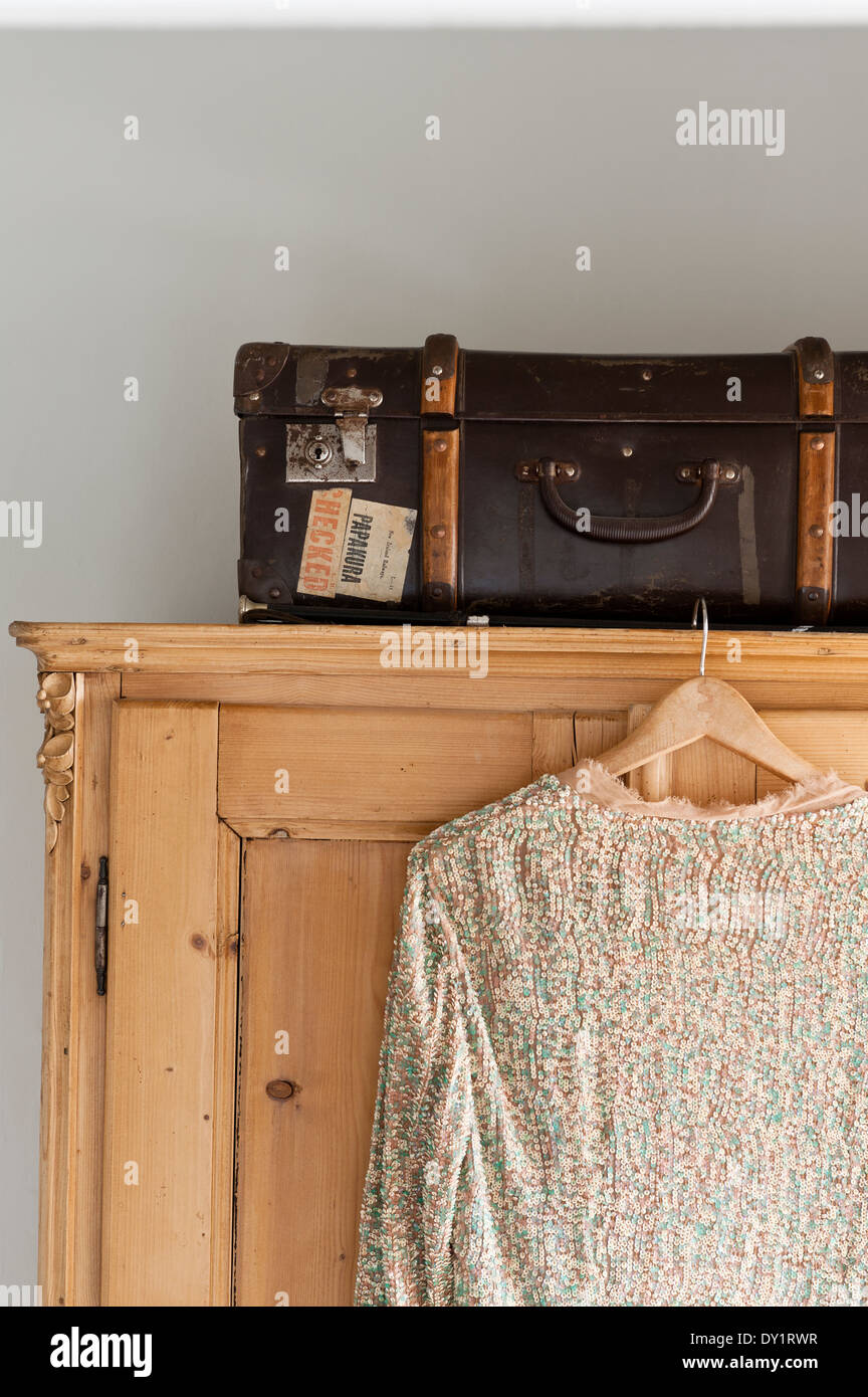 A sequined top hung from a pine cupboard with a vintage trunk on top - Stock Image