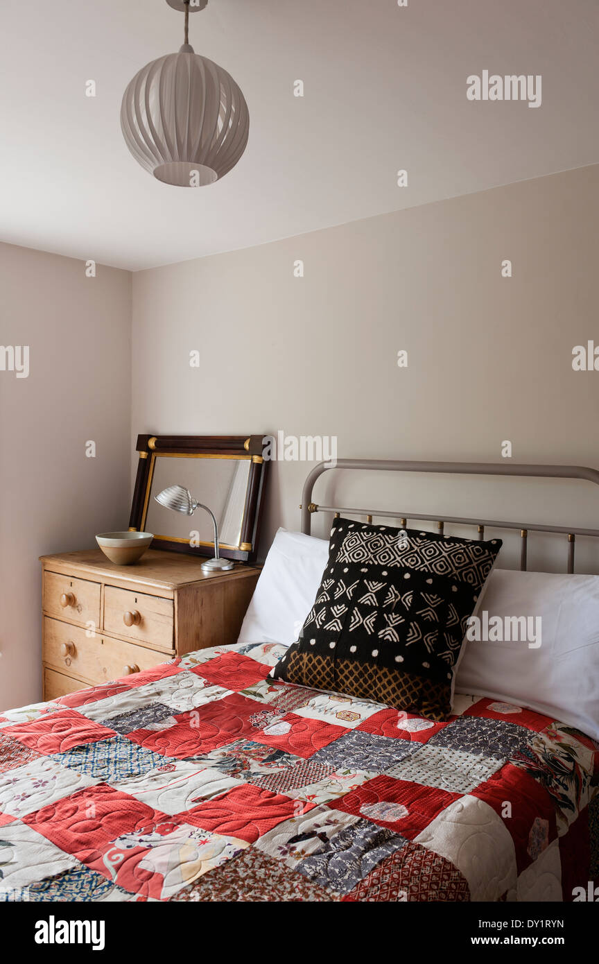 bedroom with double bed and patchwork quilt - Stock Image