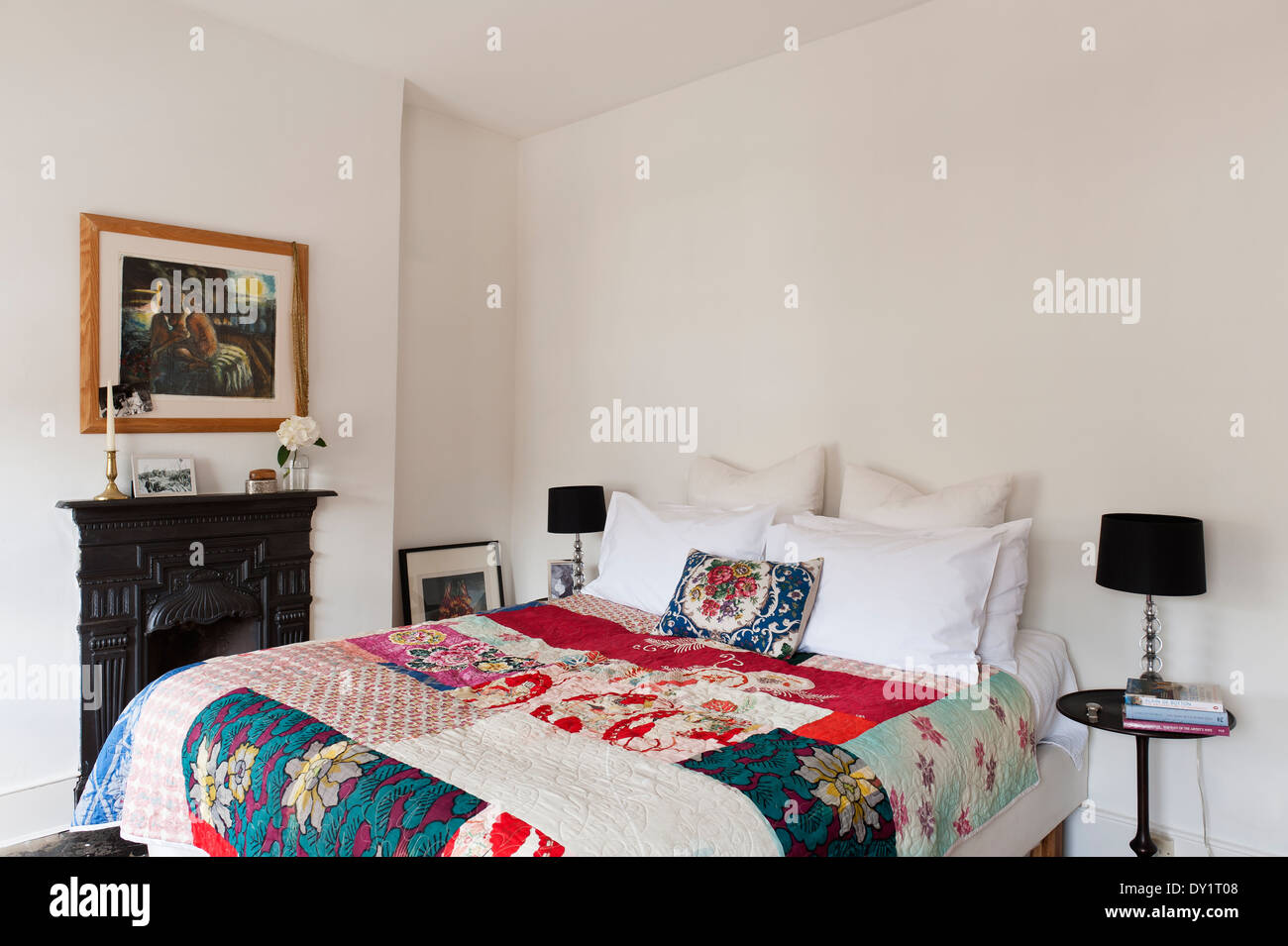 bedroom with patchwork quilt and fireplace - Stock Image