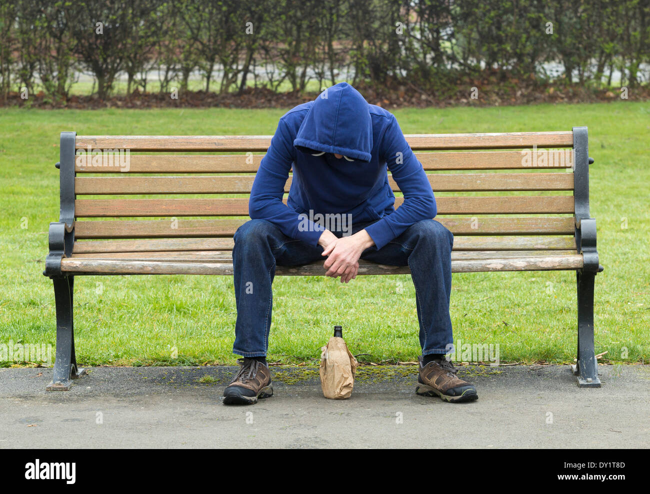 Male wearing hoodie sitting on park bench drinking alcohol - Stock Image