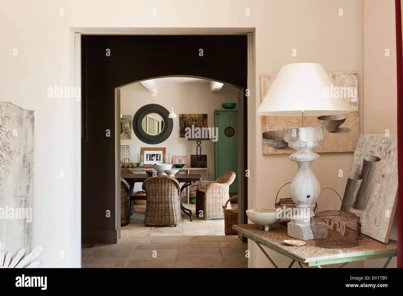 View from salon through to dining room with stone flooring. A stone lamp sits on a wrought iron folding table in the corner - Stock Image