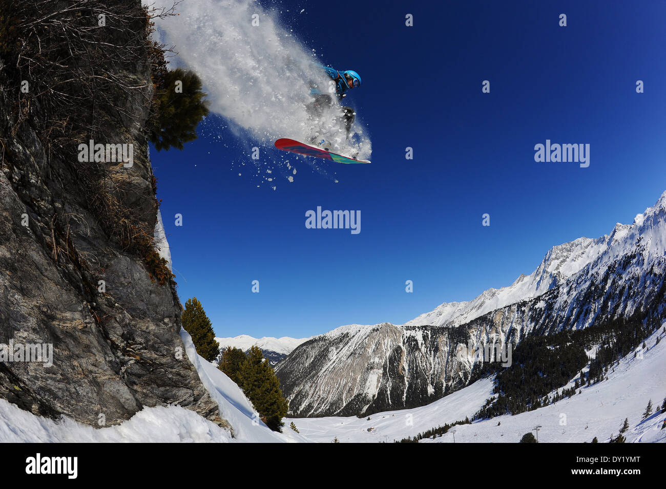A snowboarder jumps off a cliff off piste in the French ski resort of Courchevel. - Stock Image