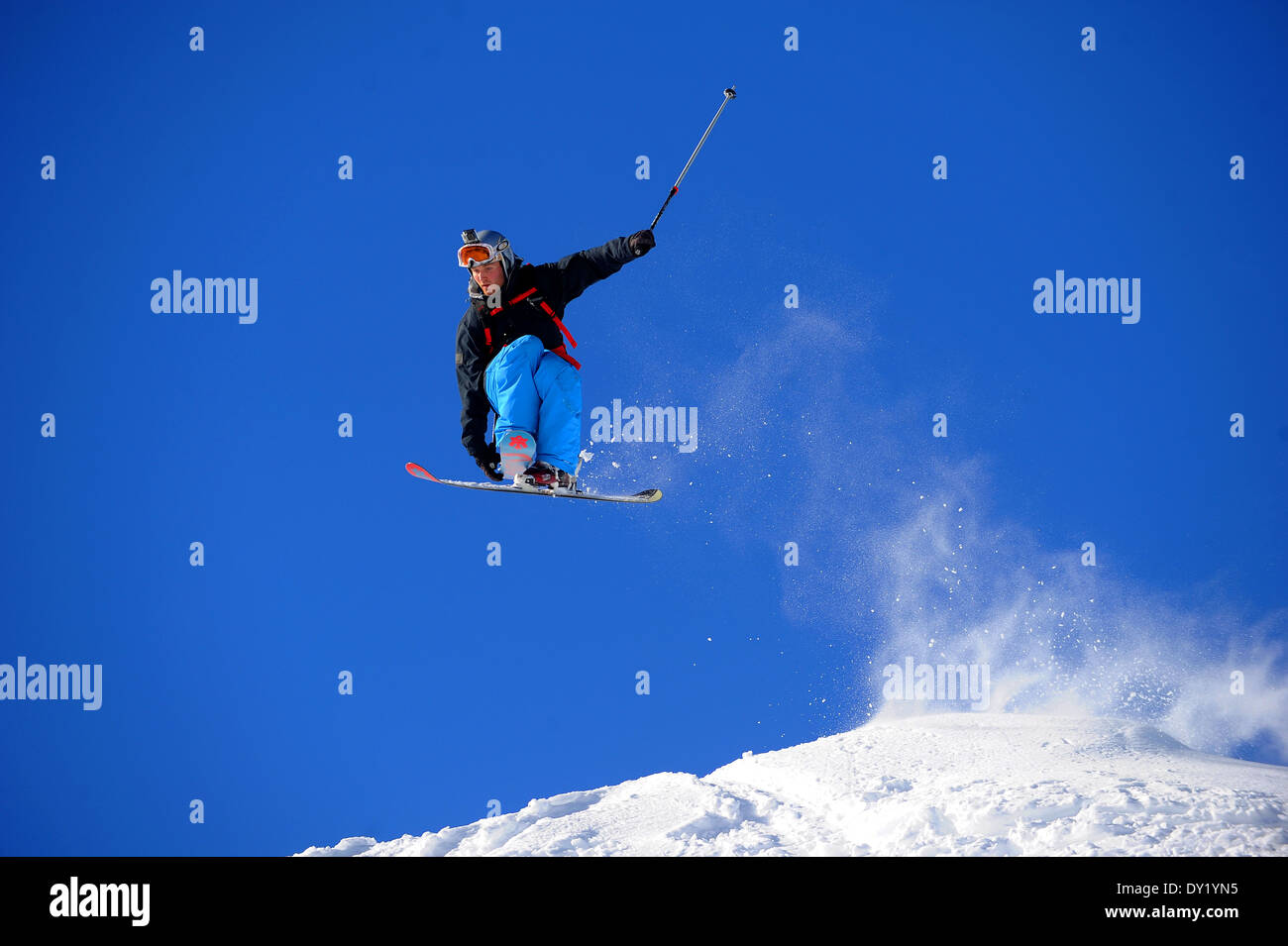 A skier performs a grab as he jumps off piste in the French ski resort of Courchevel. - Stock Image