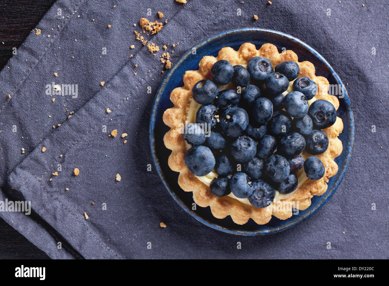 Top view on blueberry tart served on blue ceramic plate over textile napkin. - Stock Image