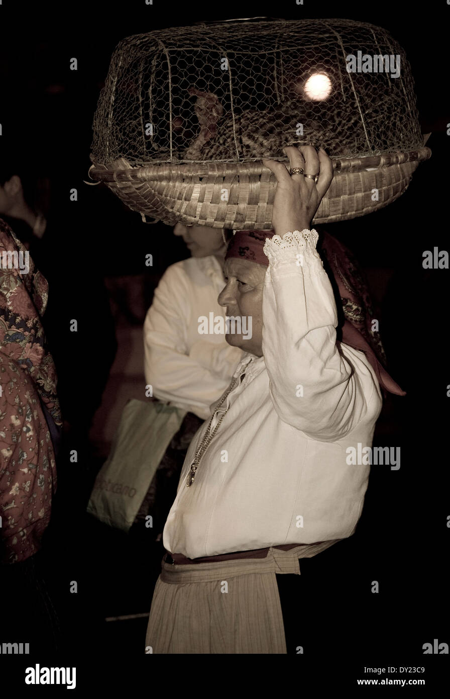 An elderly woman carrying a cage with a hen on her head in the traditional Porto's parade - Stock Image