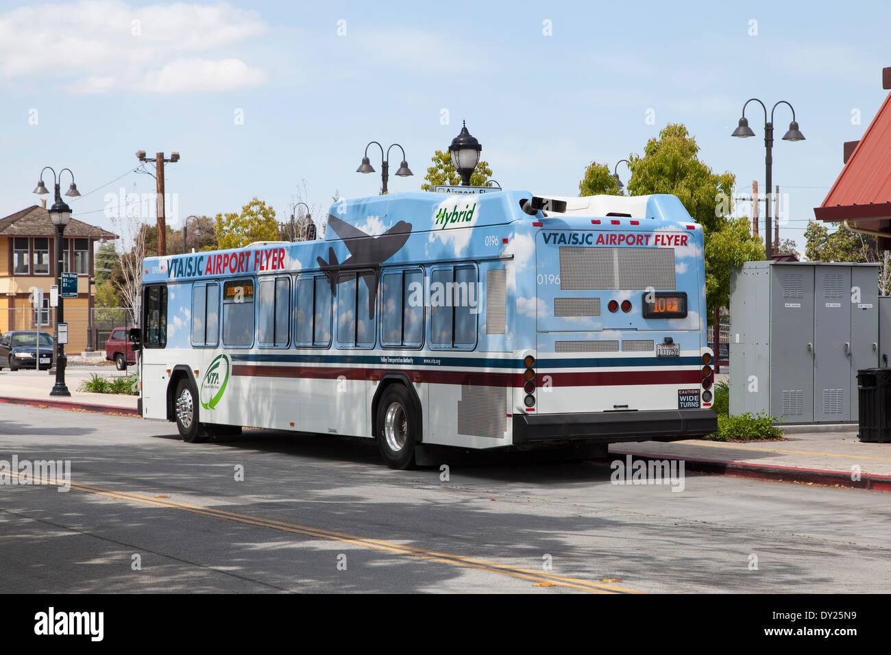 A VTA hybrid bus awaits passengers at the Cal Train Station in Santa Clara, CA. - Stock Image