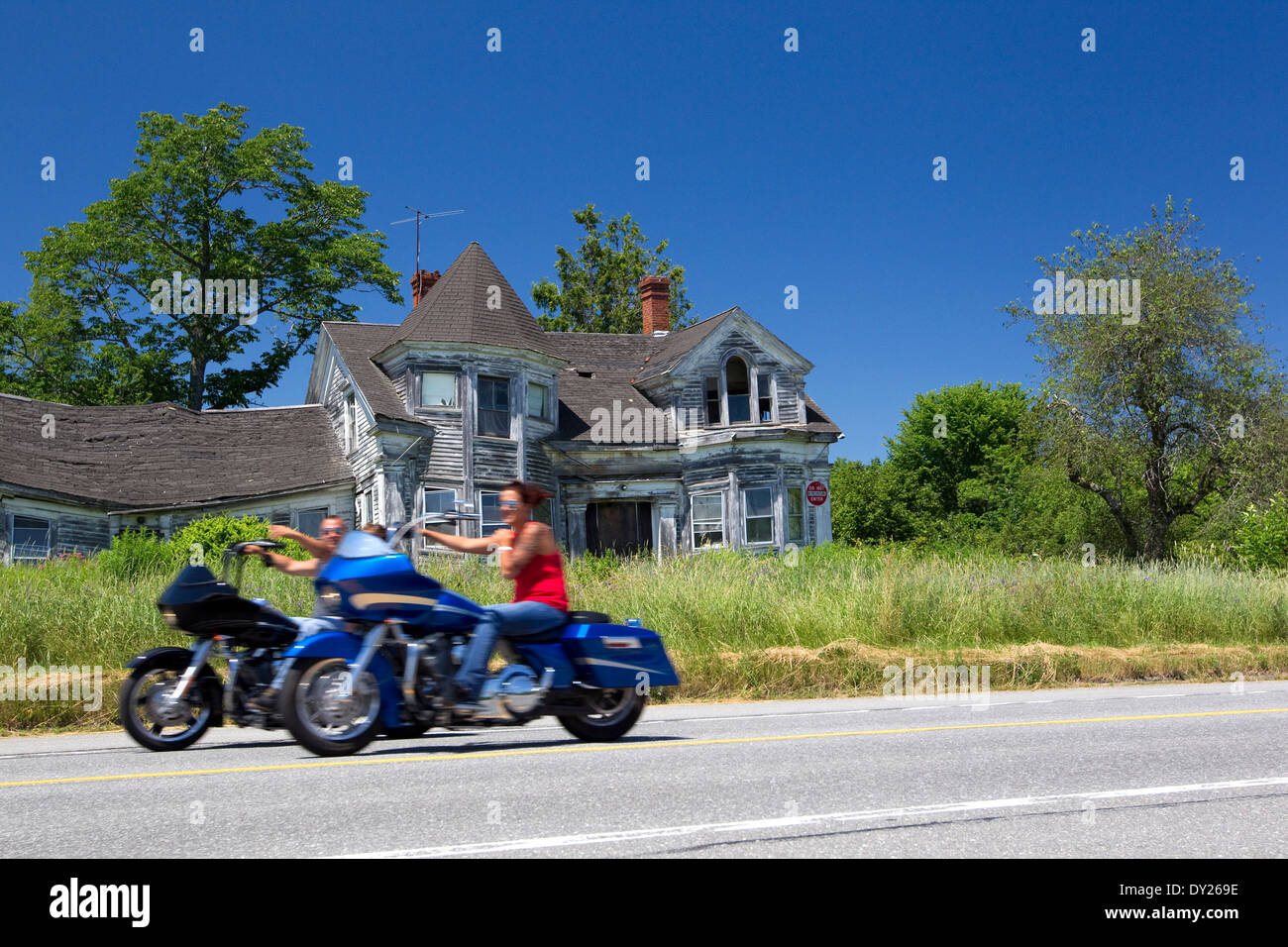 Motorcyclists ride by an abandoned, dilapidated old house from a bygone era, Maine, USA - Stock Image