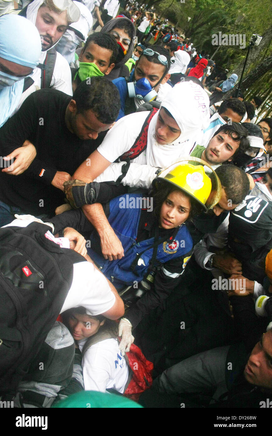 Caracas, Venezuela - April 3, 2014: A group of violent demonstrators tries to lynch an infiltrate in a protest in the Central University of Venezuela, while another group supported by several firefighters tries to save him.   Credit:  Rafael A. Hernández/Pacific Press/Alamy Live News - Stock Image