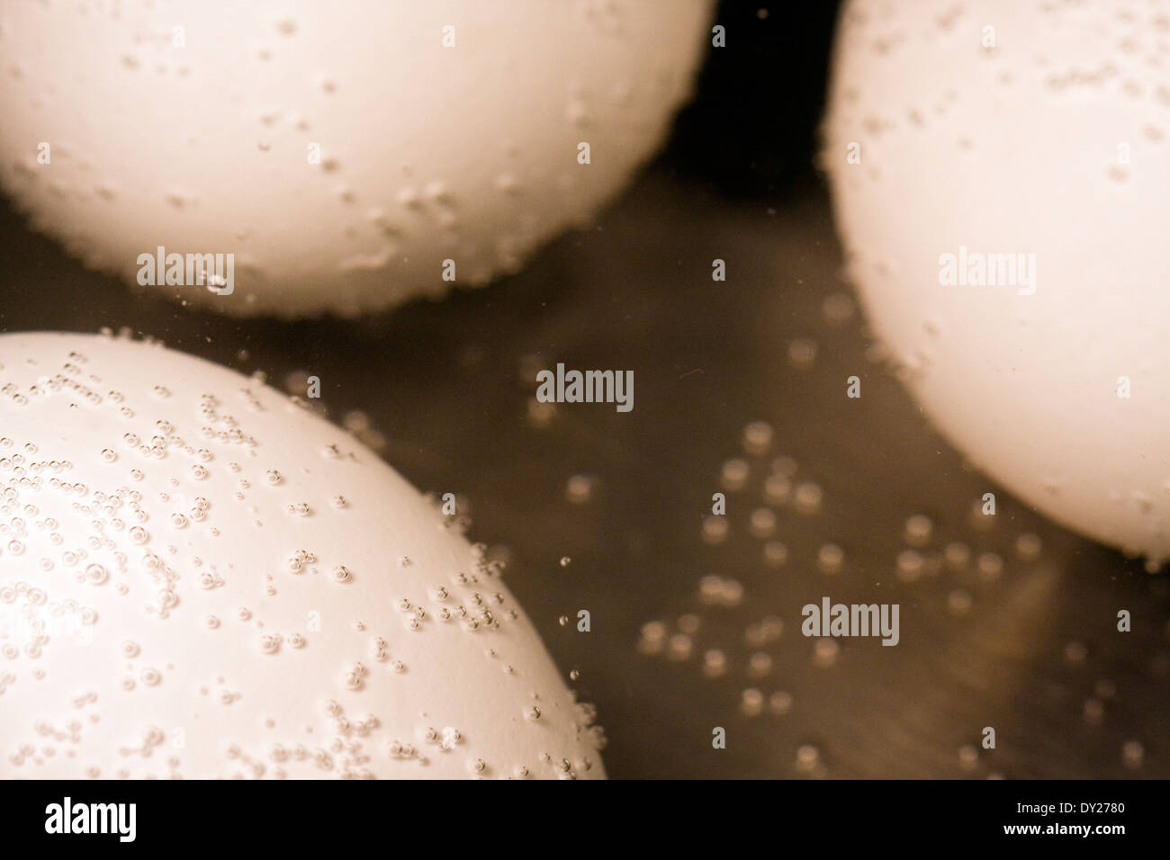 Bubbles appear on three white eggs beginning to cook in a pot of water - Stock Image