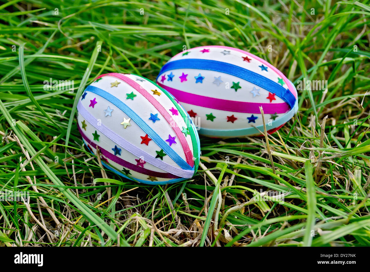 Two easter eggs, decorated with multicolored braid and sparkles as asterisks on the green grass - Stock Image