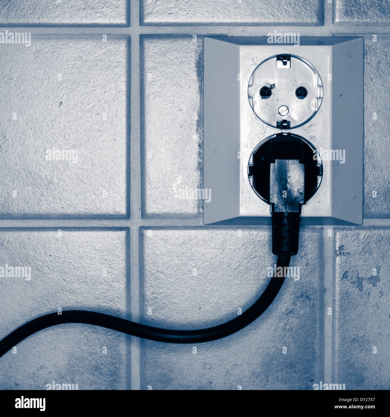 Plugged power cord in wall socket, tinted black and white image - Stock Image
