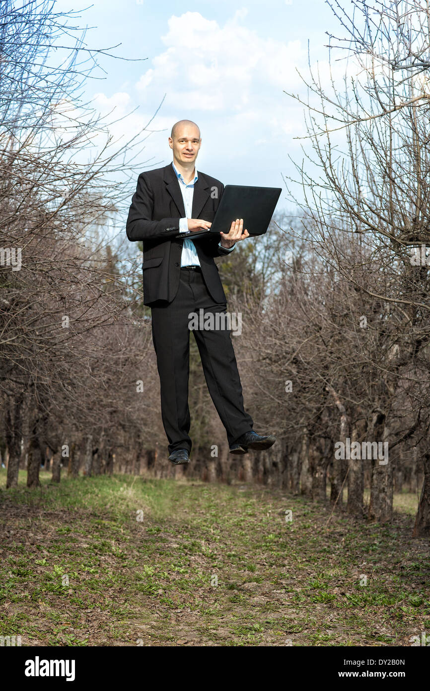 man holding a laptop and levitates. - Stock Image
