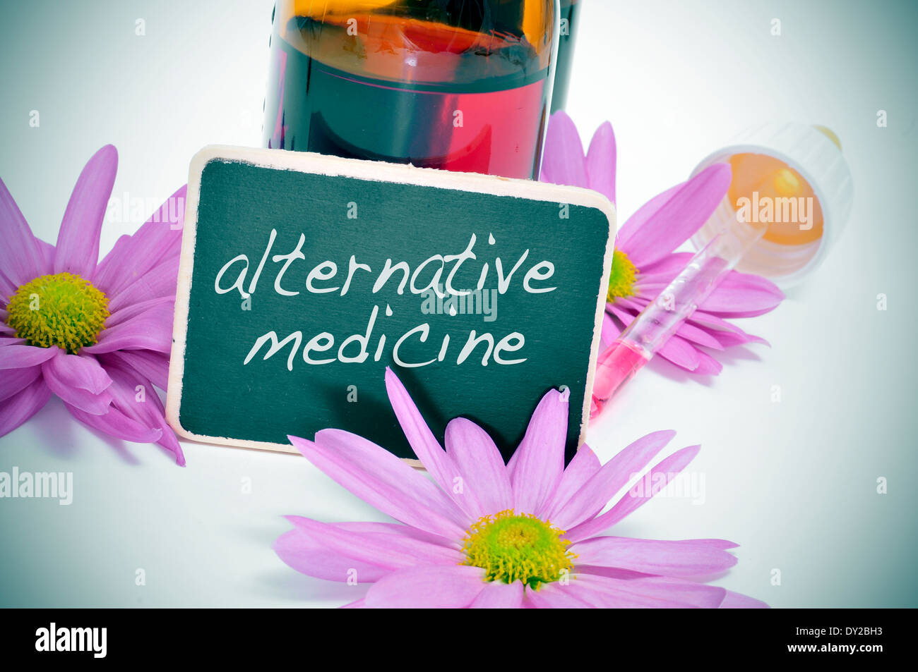 a dropper bottle and some flowers with a blackboard label with the text alternative medicine written on it - Stock Image