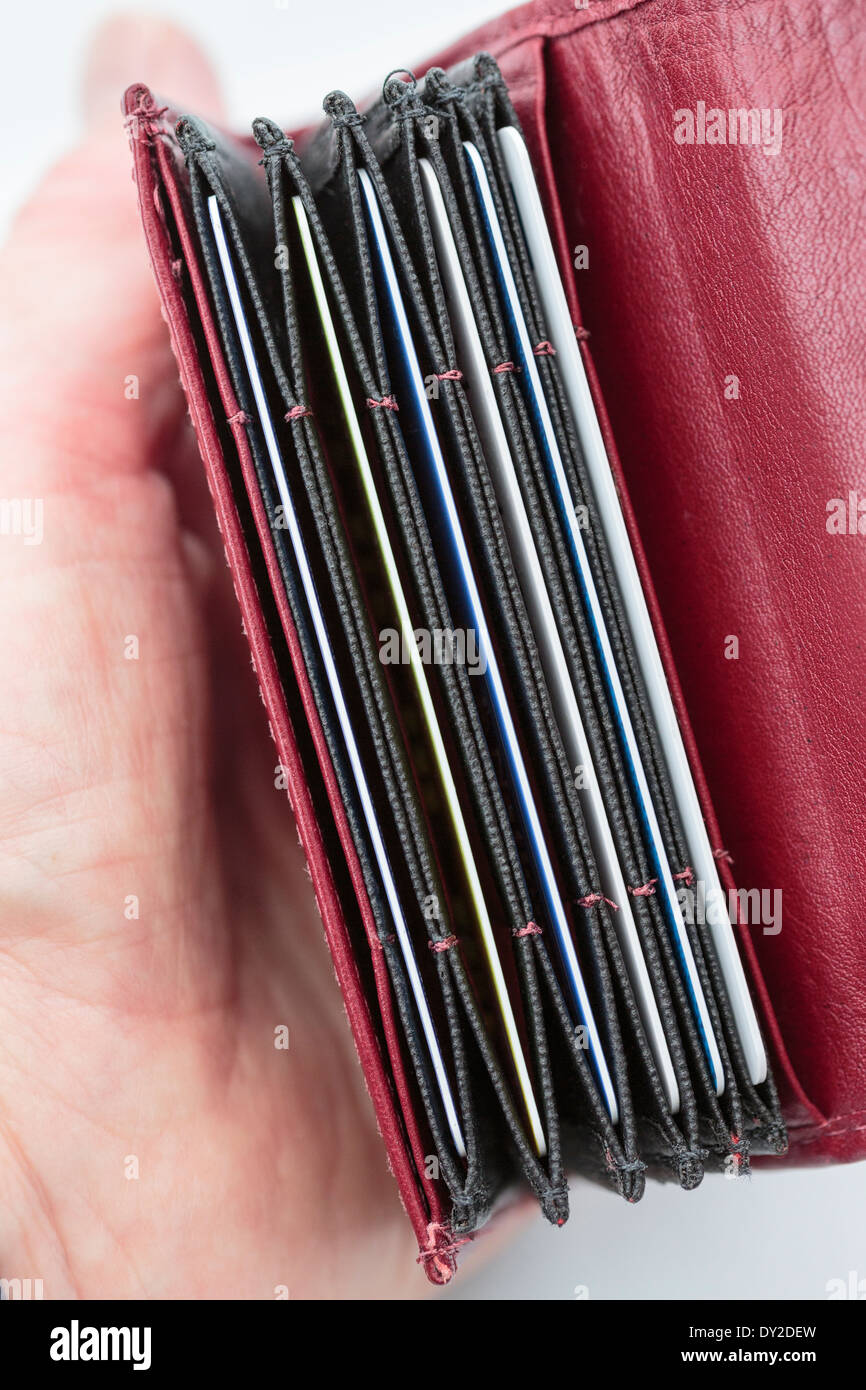 Woman's hand holding an open red card holder wallet with slots containing bank debit and credit cards. England UK Britain - Stock Image