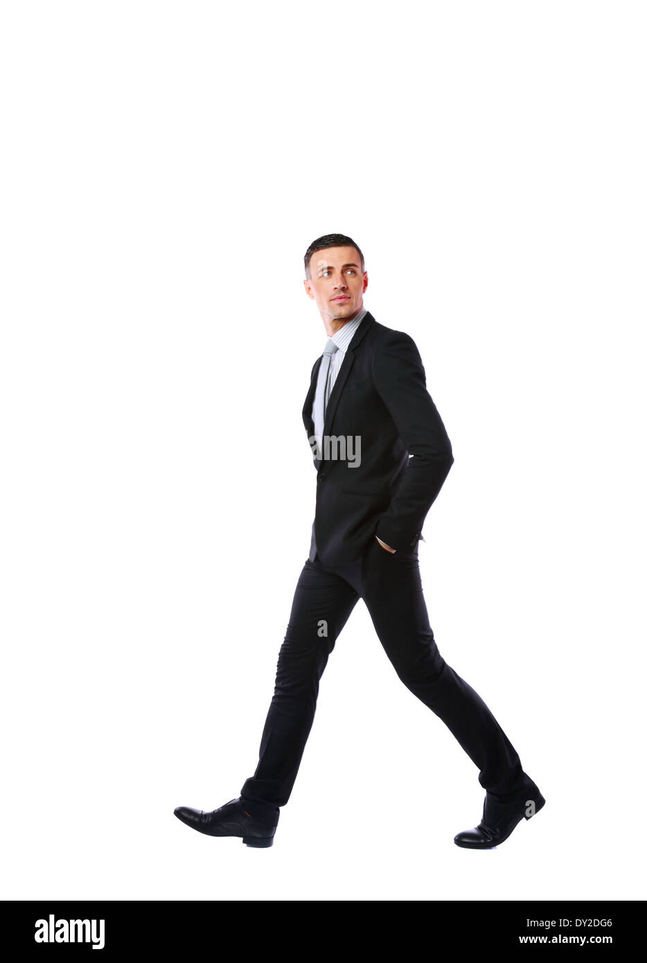 Side view portrait of a businessman walking isolated on a white background - Stock Image