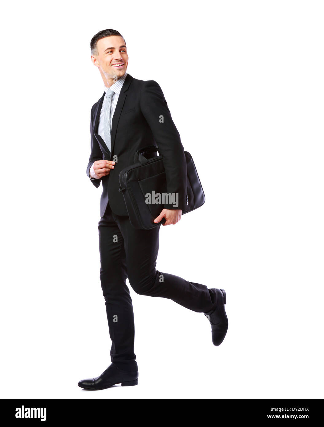 Businessman walking with laptop bag isolated on a white background - Stock Image