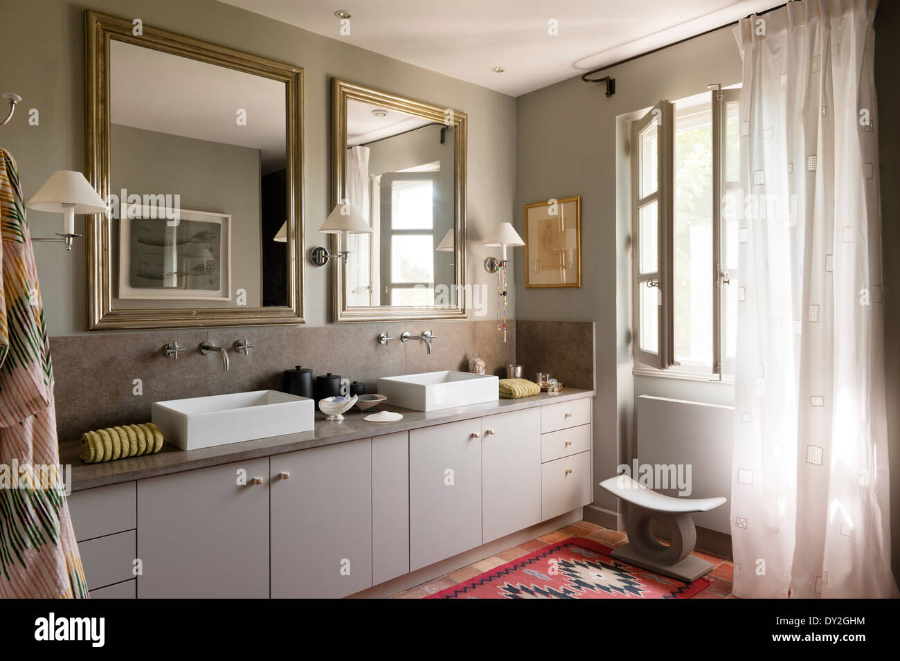 Modern square basins and mirrors in bathroom in grey tones and with ethnic rug. The wall paint is by Emery & Cie - Stock Image
