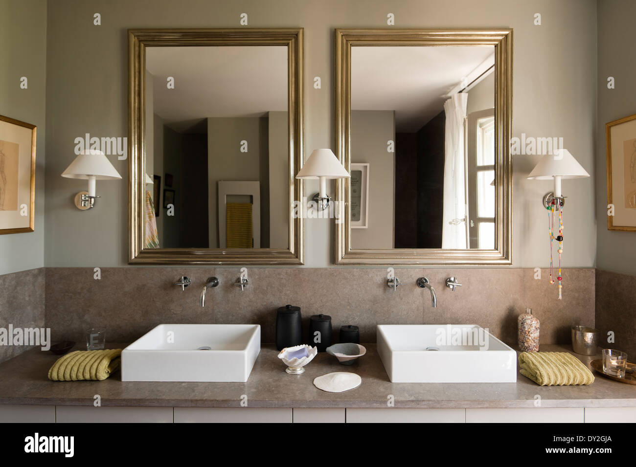 Modern twin square basins and mirrors in bathroom in grey tones. The wall paint is by Emery & Cie - Stock Image
