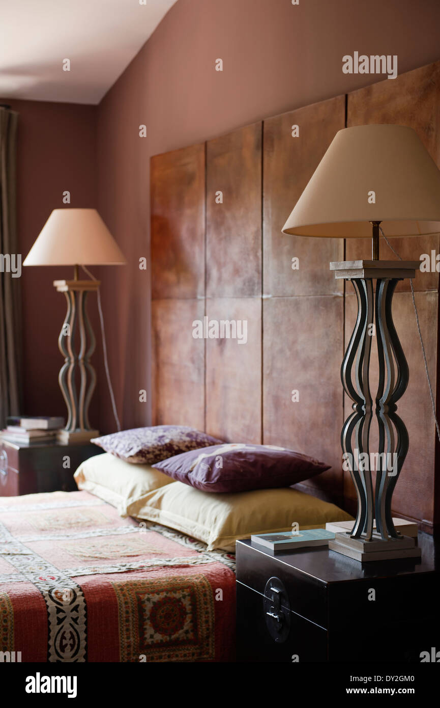 1940's leather screen behind bed flanked by vintage iron lamps in bedroom with wall paint by Emery & Cie and - Stock Image