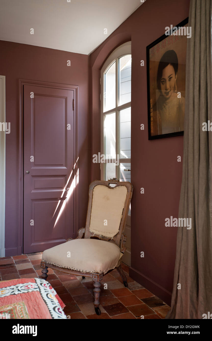 Upholstered wooden french chair in bedroom with terracotta floor tiles and Emery & Cie wall paint - Stock Image