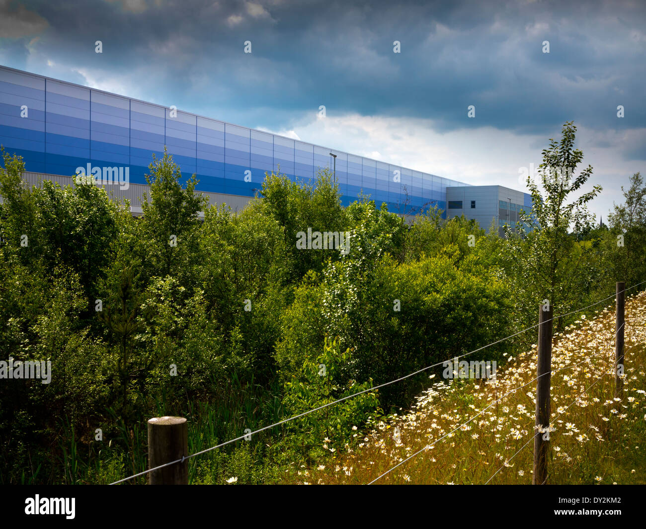 Exterior of Amazon UK warehouse in Rugeley Staffordshire England with stormy sky above and trees in foreground Stock Photo