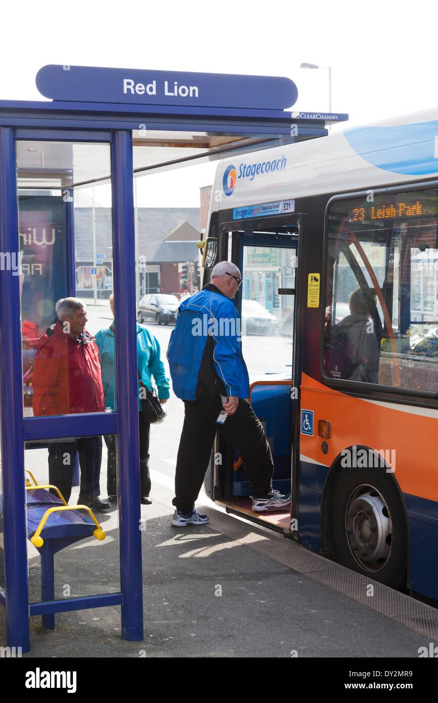 Passengers boarding single decker bus at bus stop. - Stock Image