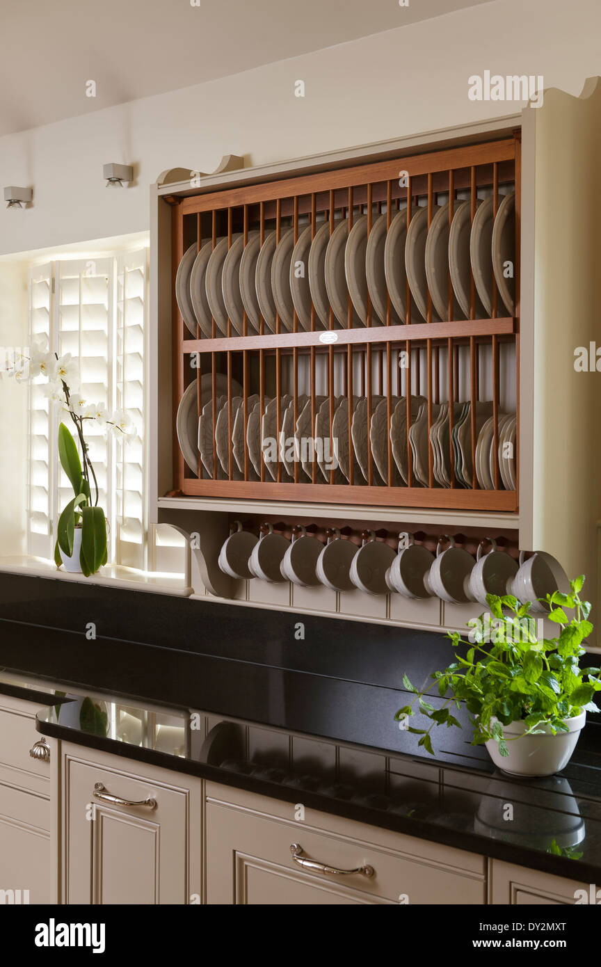 Wooden plate drying rack above a black granite worktop with basil plant & Wooden plate drying rack above a black granite worktop with basil ...
