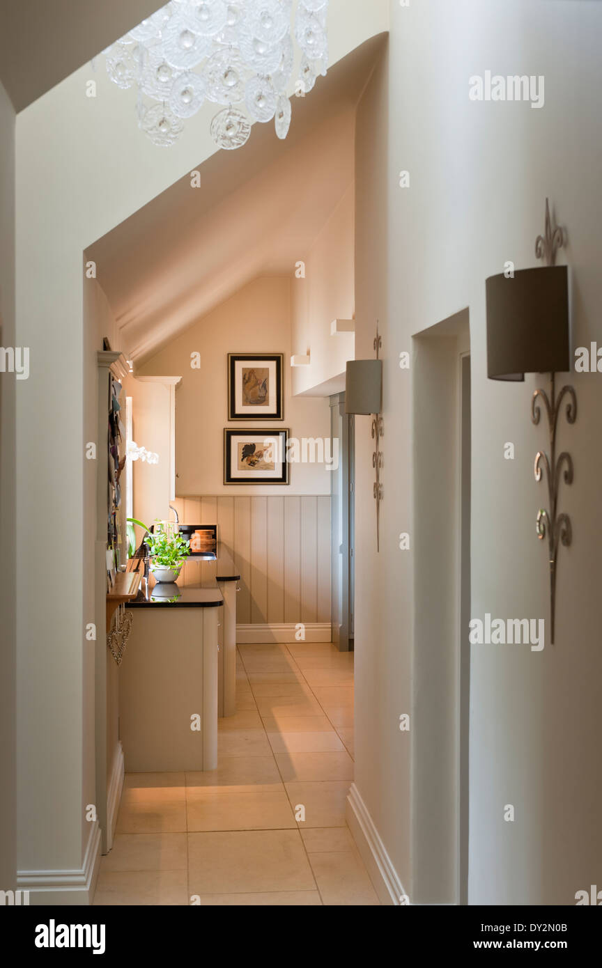 Corridor with slanted ceiling, glass chandelier and stylish wall sconces - Stock Image