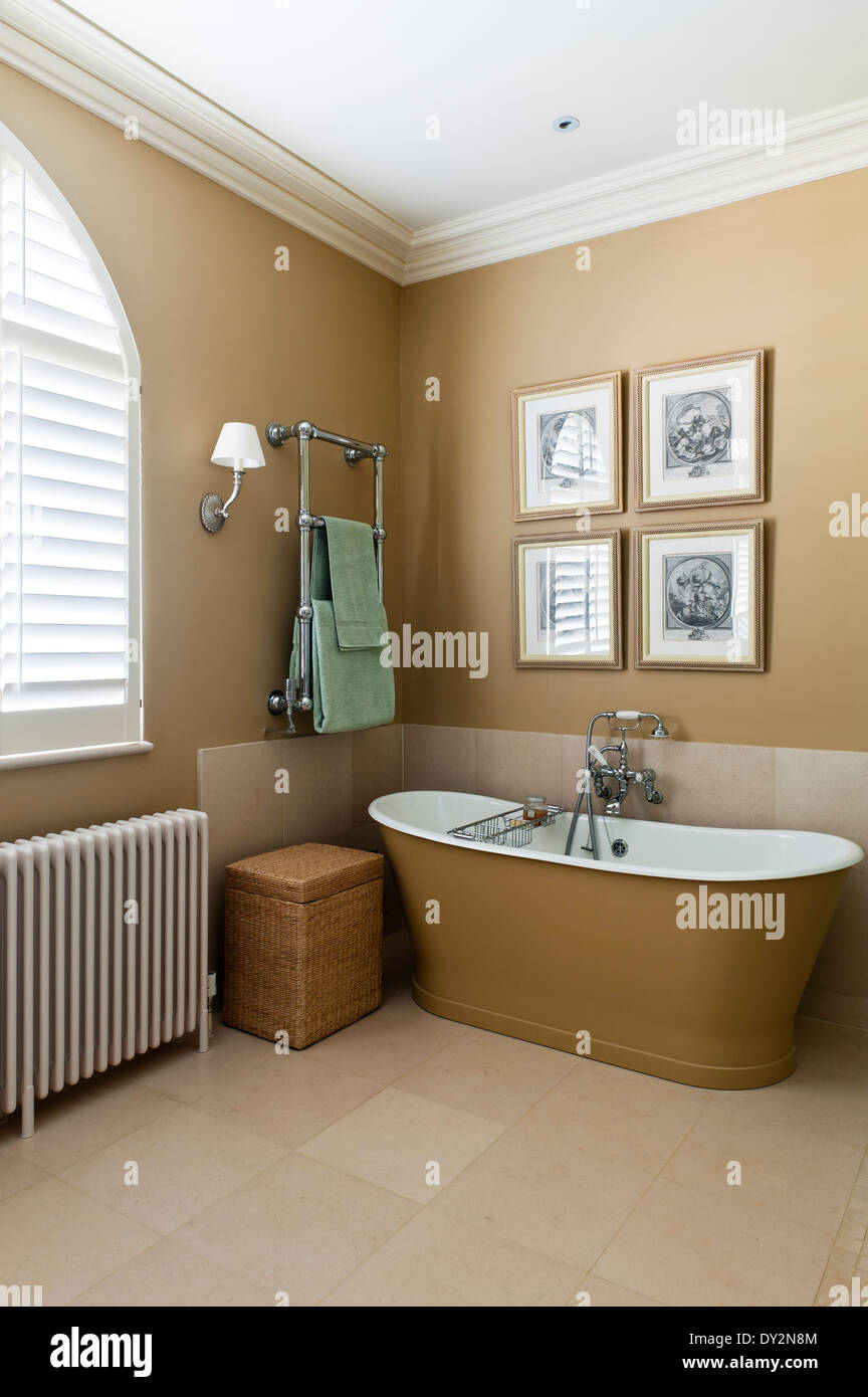 Double-ended free standing bath from Drummonds in bathroom with stone flooring. The taps are by Perrin and Rowe - Stock Image