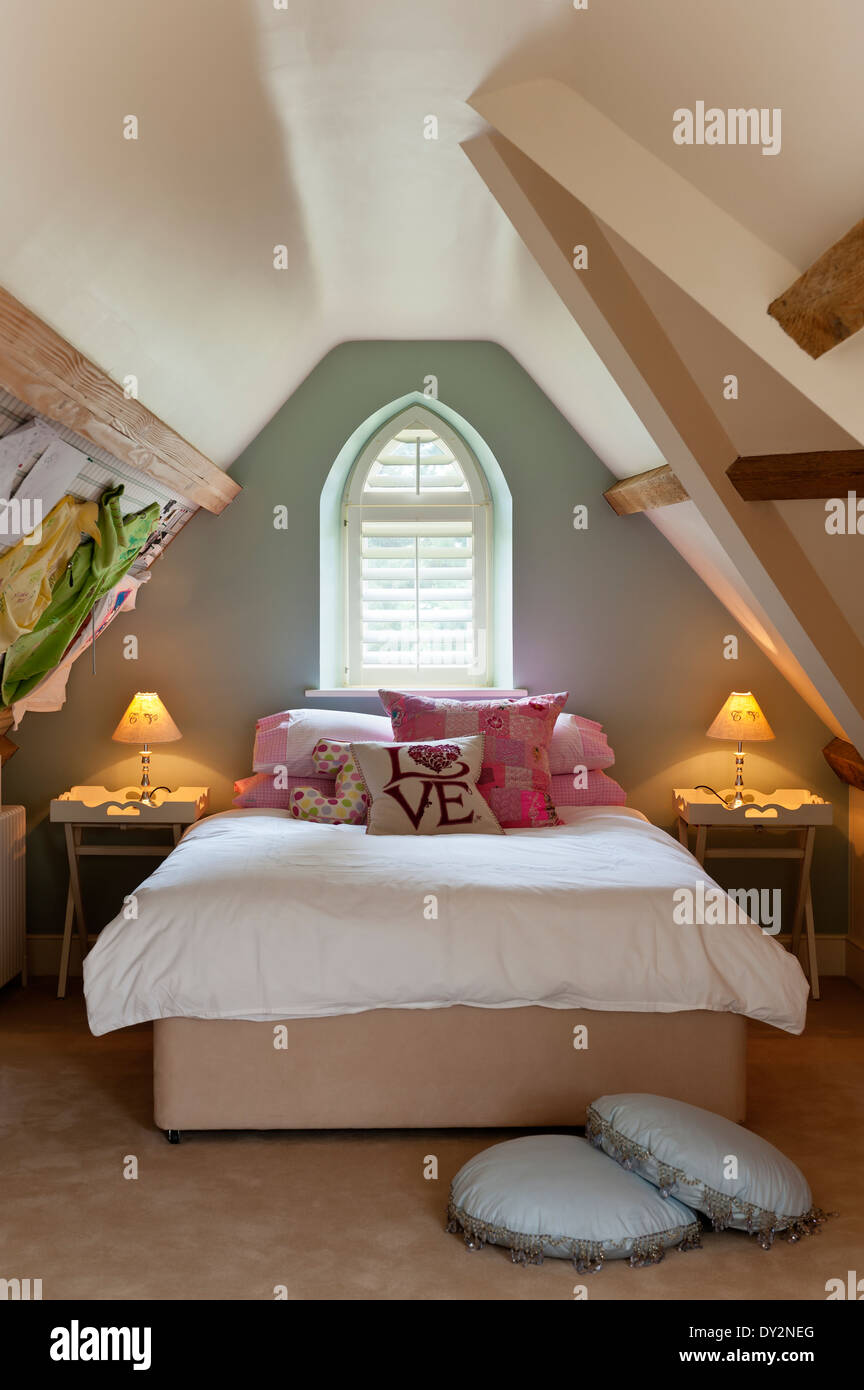 Girls attic bedroom with sloping walls and arched window - Stock Image