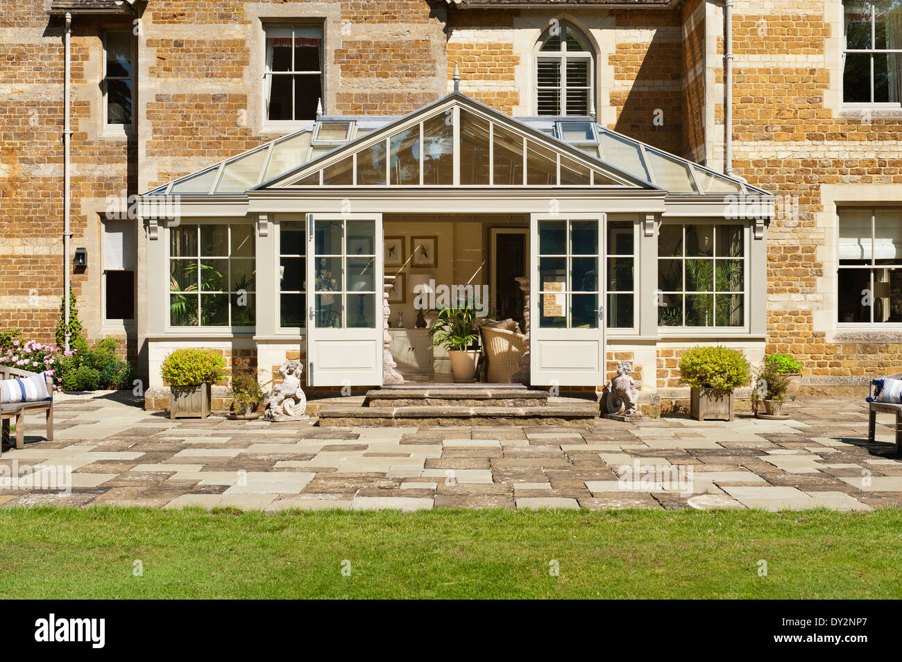 Exterior facade of a conservatory added to 19th century farmhouse with stone patio and lawn - Stock Image