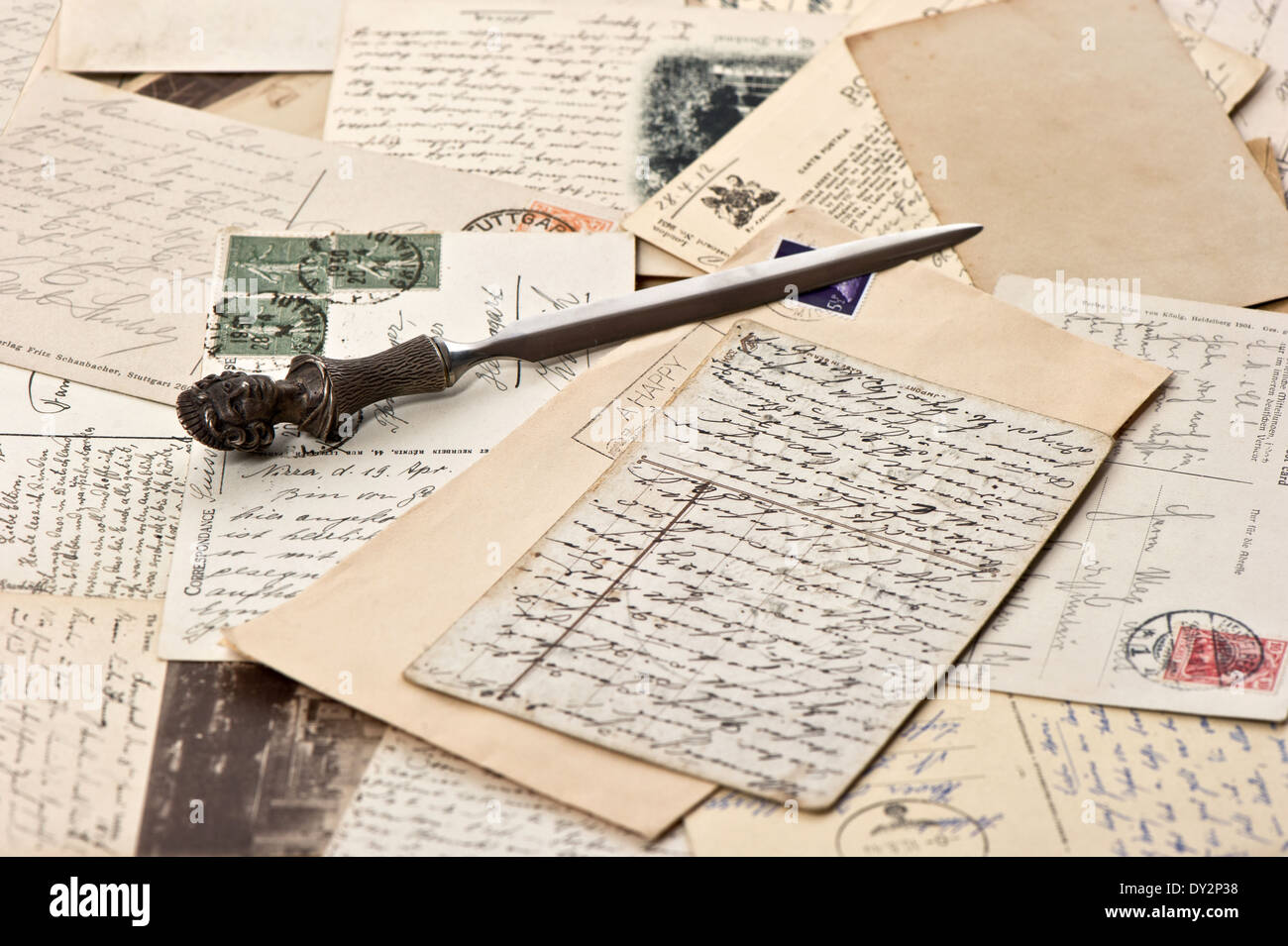 old papers and post cards with letter opener. vintage grunge background. selective focus - Stock Image