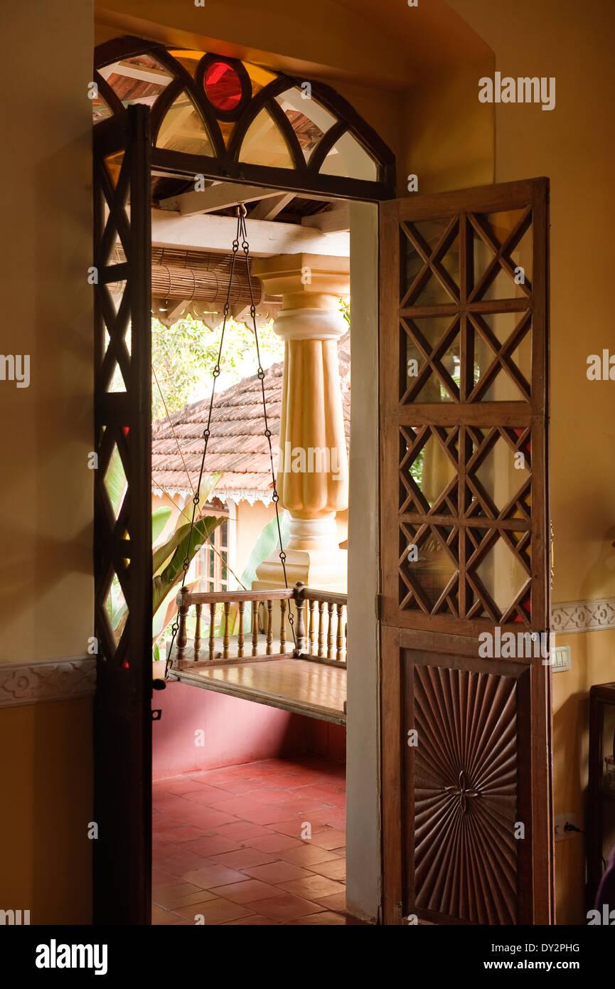 View through doorway to swing seat on veranda of Goan home - Stock Image