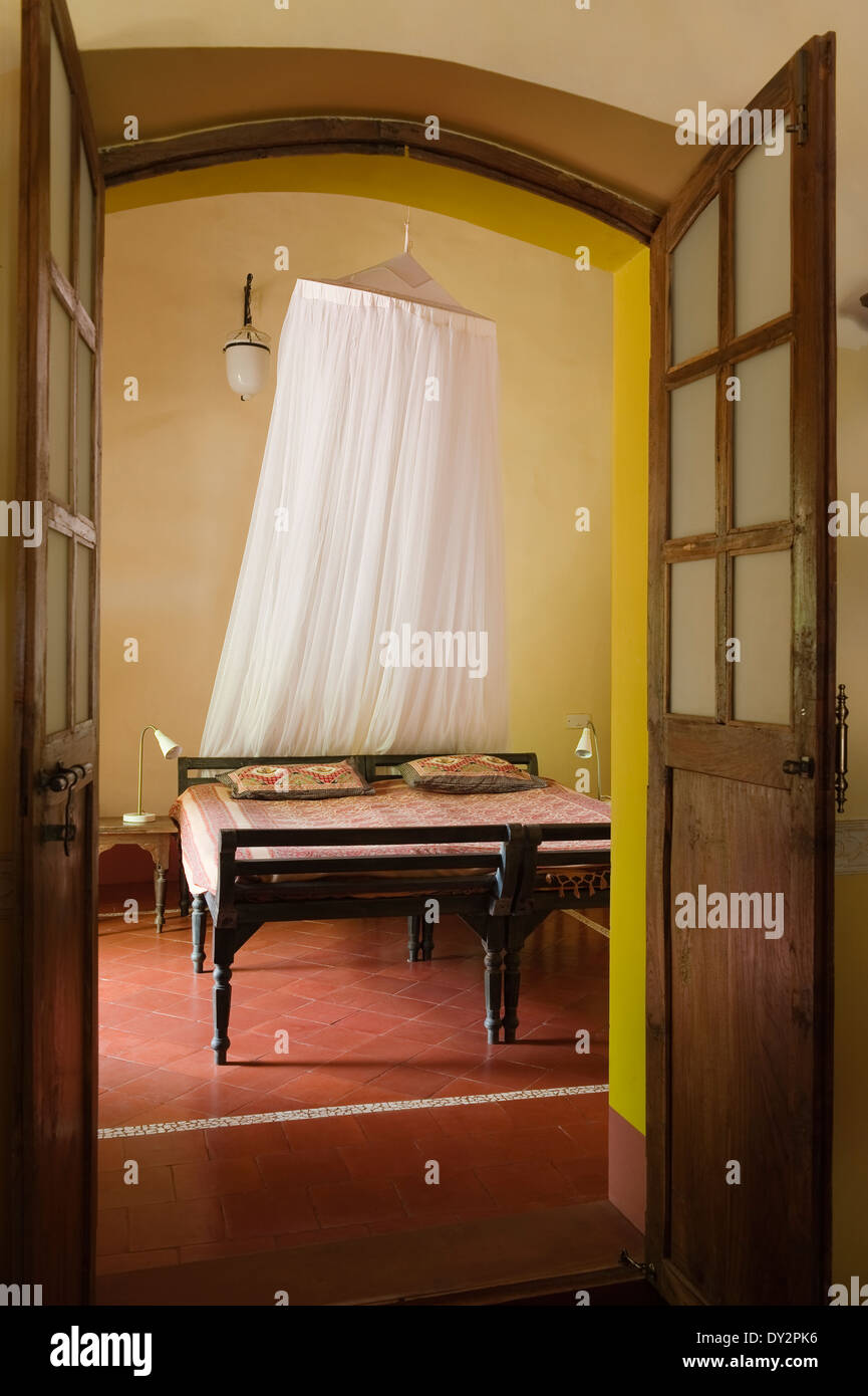 View into bedroom through double doors in Goan home, India ...