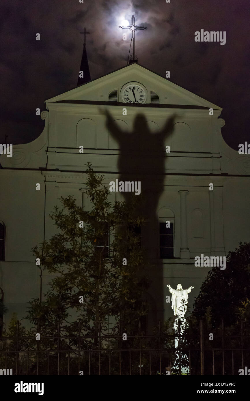 Full moon partially occluded by an iron cross and the shadow a Jesus statue at the rear of St. Louis Cathedral in New Orleans - Stock Image