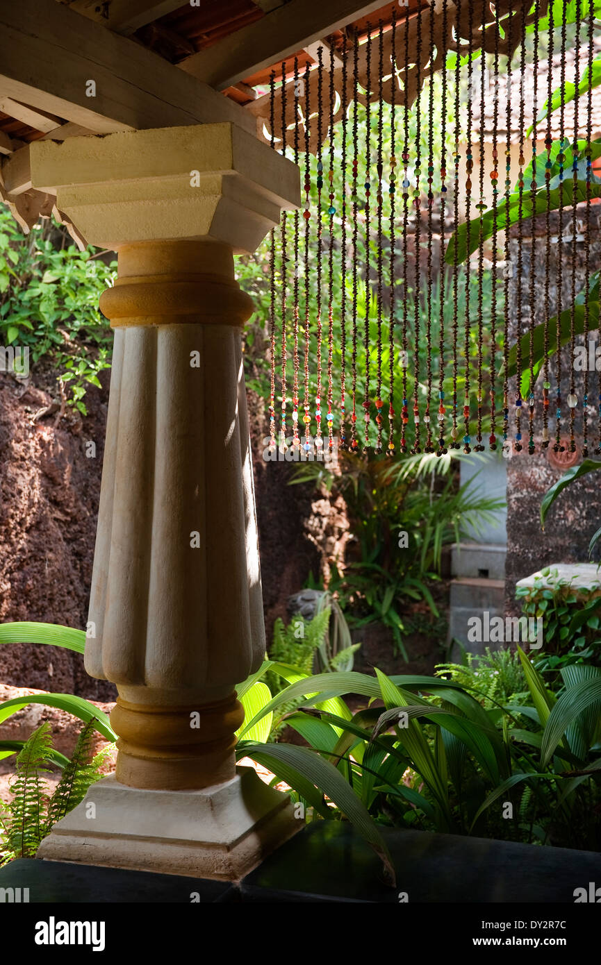 Beaded curtain and pillar in garden of Goan home - Stock Image