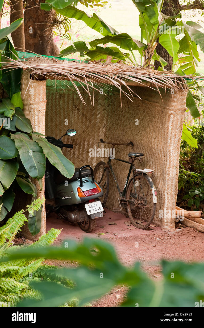 Motorbike and bicycle in bamboo shelter of Goan home - Stock Image