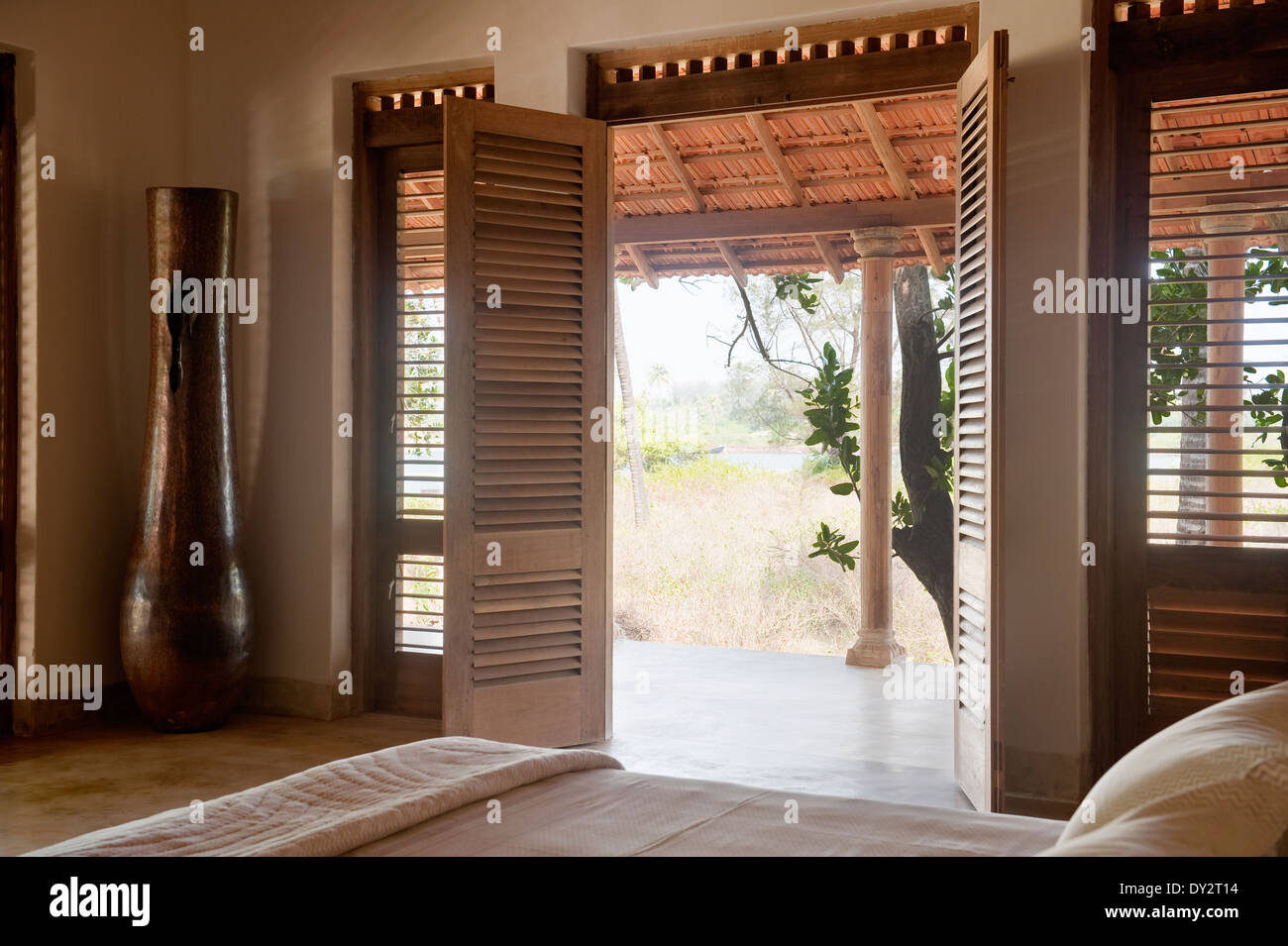 Double doors open from bedroom to veranda of Goan beach house Stock on