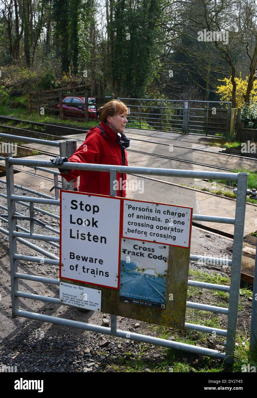 Woman pedestrian at rural railway line level crossing gate uk - Stock Image