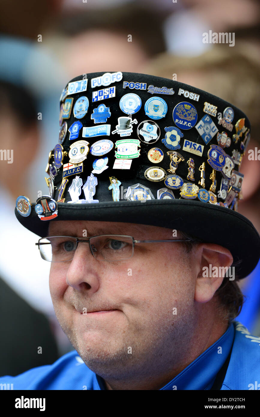 Peterborough football supporter fan wearing top hat with badges Uk - Stock Image