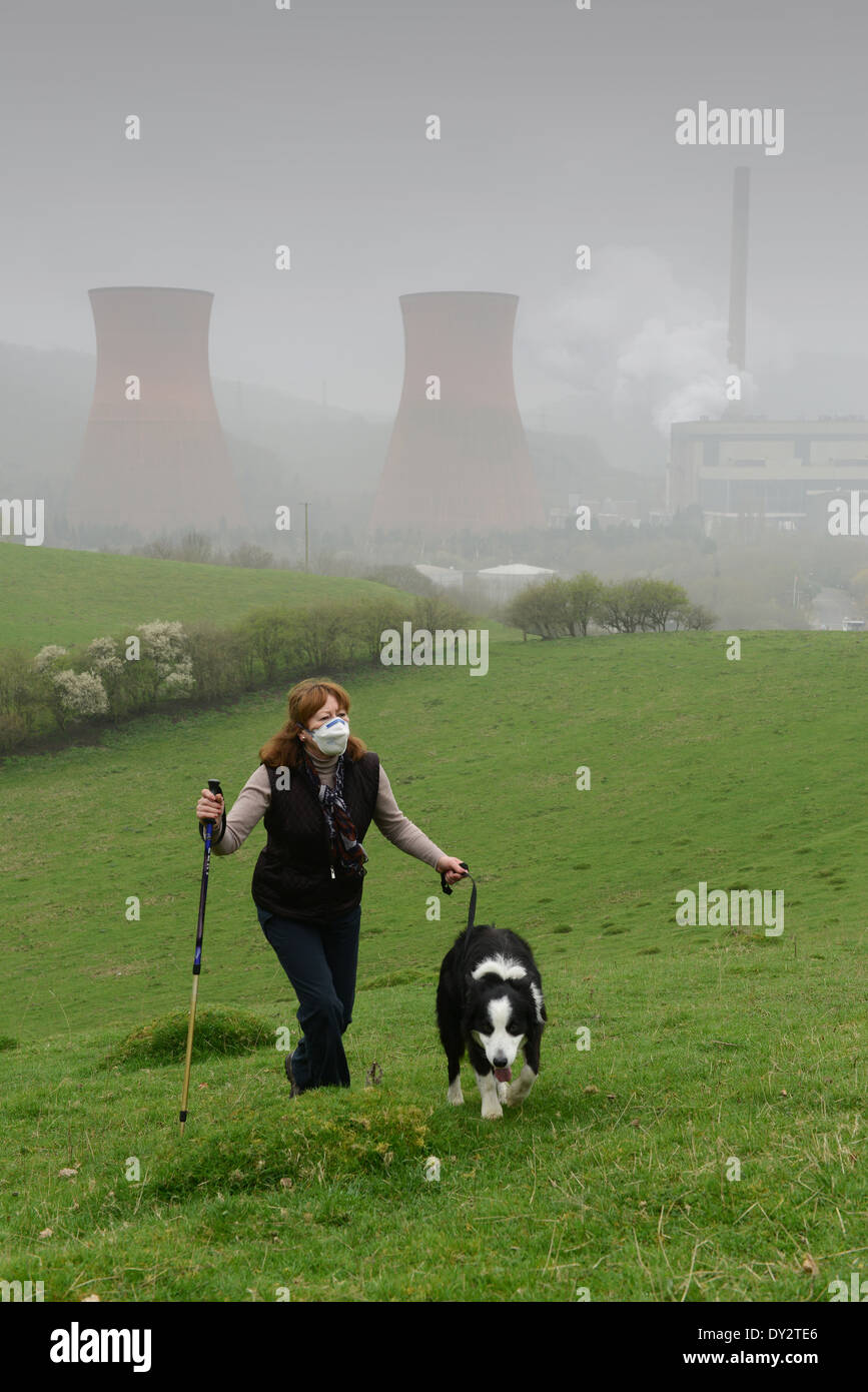 Woman wearing smog mask while walking dogs near Ironbridge Power Station due to smog pollution in UK - Stock Image
