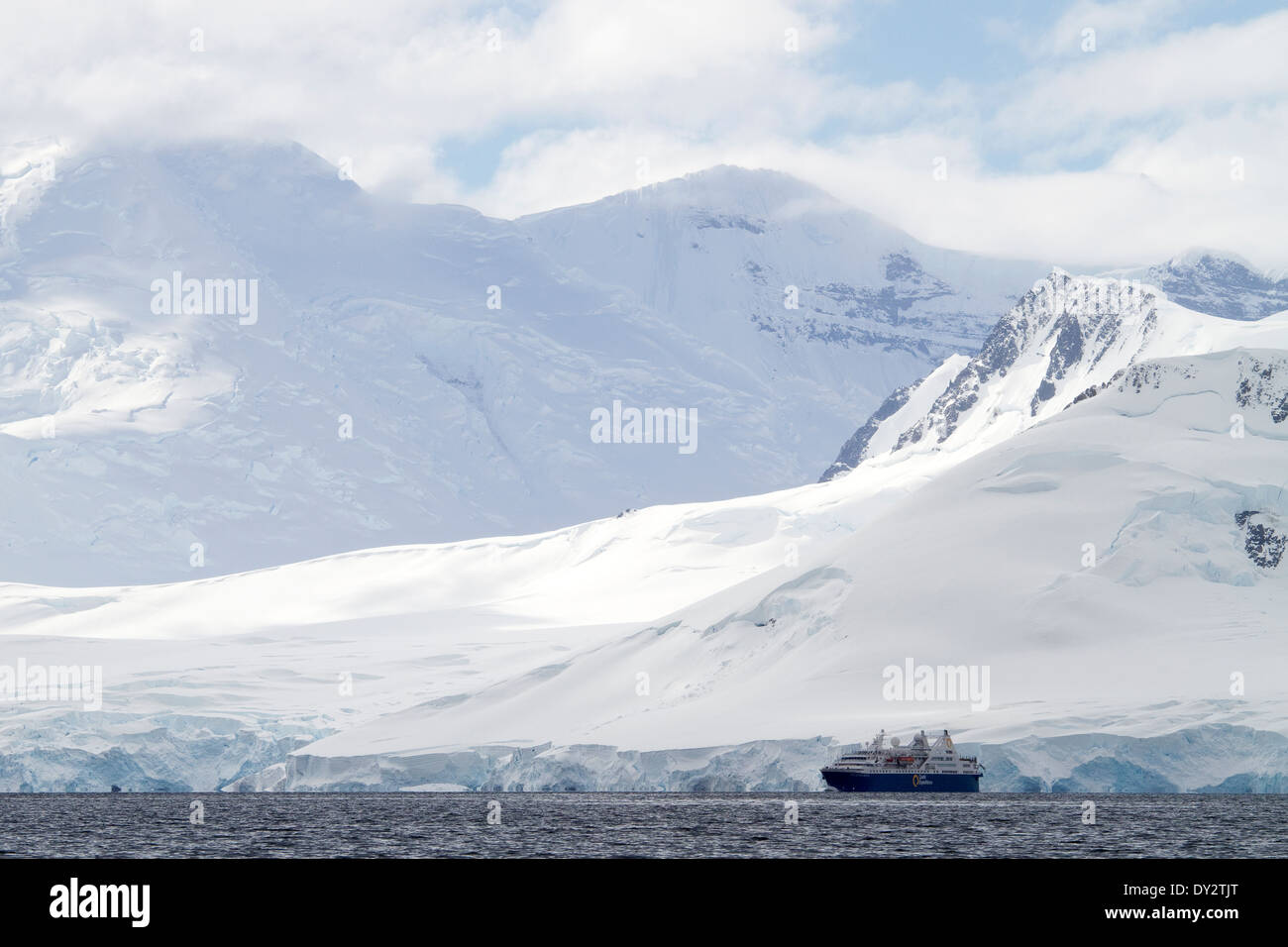 Antarctica tourism expedition cruise ship looks small in the Antarctica landscape of mountains, mountain,  Antarctic Peninsula. - Stock Image