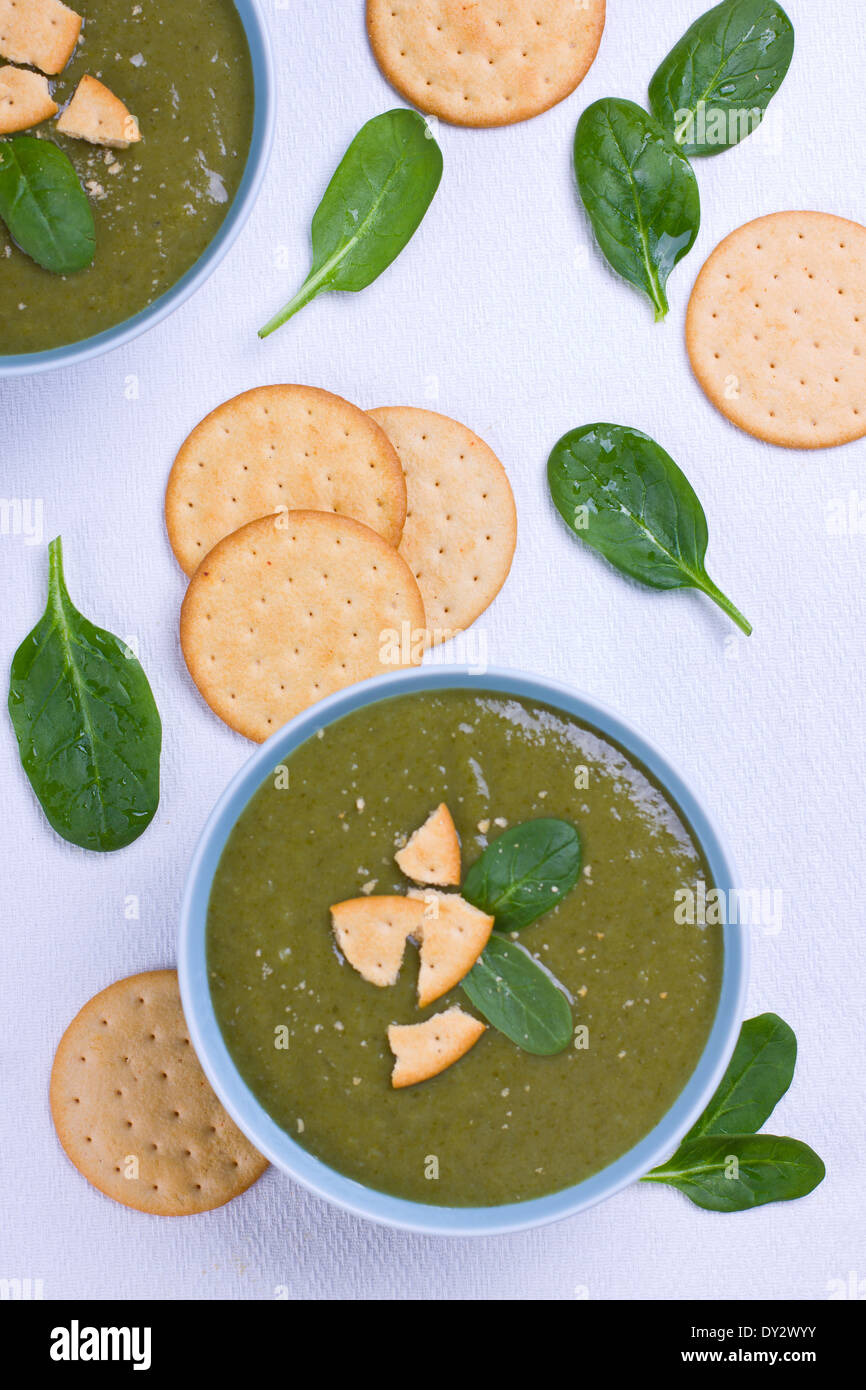 Bowl full of pureed spinach soup garnished with crackers - Stock Image