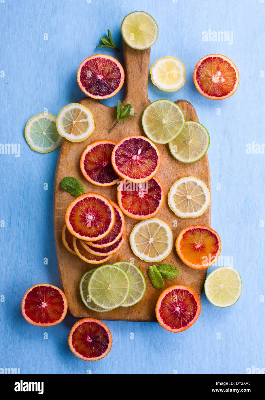 Assorted cut citrus fruits on cutting bord shot from above on light blue background - Stock Image