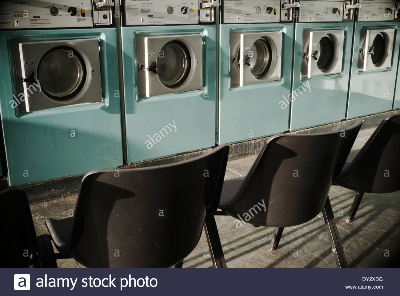 Interior of an empty launderette, with vacant seating opposite the washing machines. Stroud, UK. - Stock Image